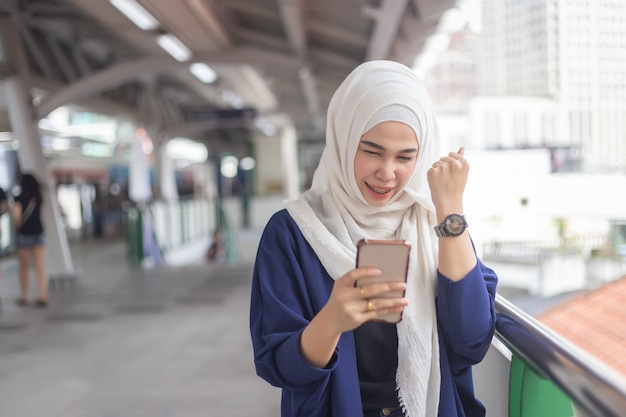 Young muslim woman using telephone on skytrain station.