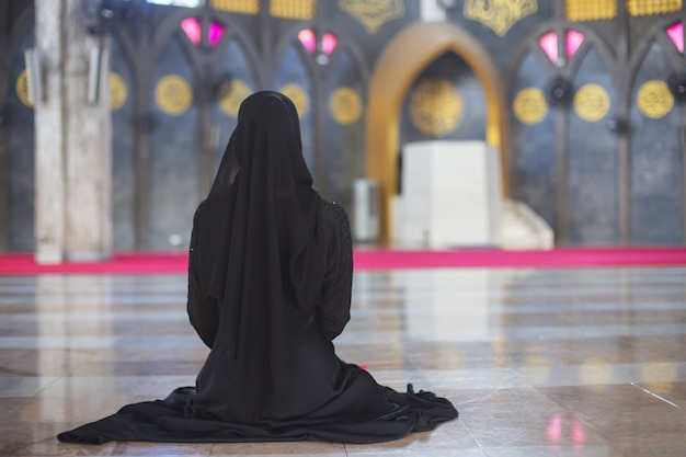 Young muslim woman in wear black dress sitting alone in mosque, rear view.