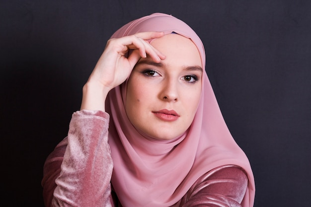 Young muslim woman wearing hijab in front of black surface