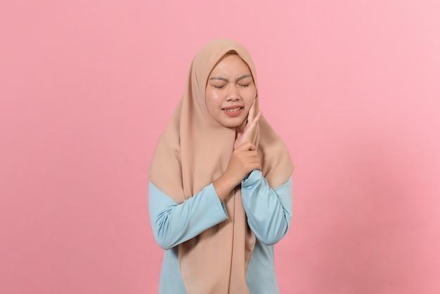 Молодая мусульманка в хиджабе на изолированном розовом фоне, касаясь рта рукой с болезненным выражением лица из-за зубной боли или стоматологического заболевания на зубах. концепция стоматолога.