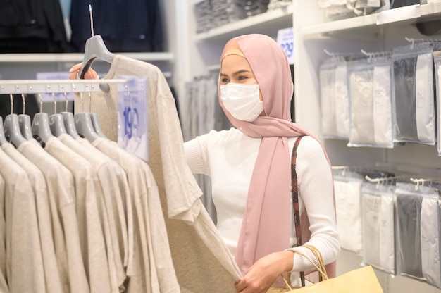 A young muslim woman wearing protective mask in shopping mall, shopping under covid-19 pandemic concept.