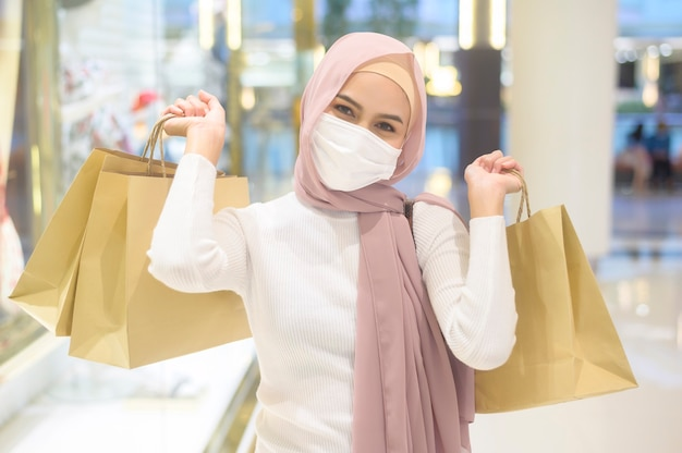Young muslim woman wearing protective mask in shopping mall