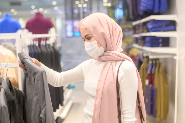 A young muslim woman wearing protective mask in shopping mall