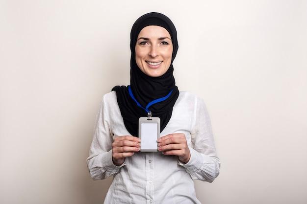 흰색 셔츠와 그녀의 사무실 배지를 보여주는 히잡을 입고 젊은 무슬림 여성