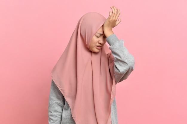 Молодая мусульманка с головной болью держит за виски рукой. концепция здоровья, мигрени и головной боли, изолированная на розовом фоне