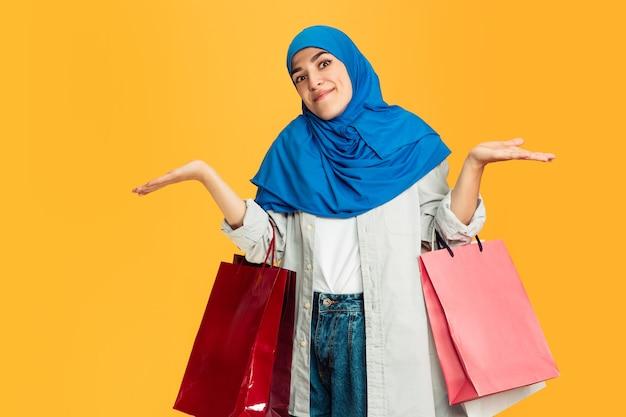 黄色のカラフルなショッピングパッケージを持つ若いイスラム教徒の女性。
