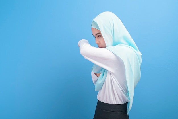Young muslim woman with hijab  feeling sick and coughing over blue background studio.