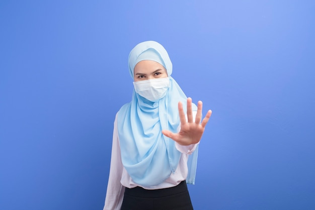 A young muslim woman with hijab wearing a surgical mask over blue wall.