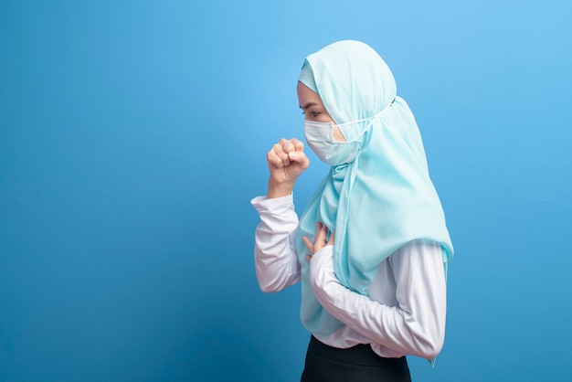 A young muslim woman with hijab wearing a surgical mask feeling sick and coughing over blue background studio.