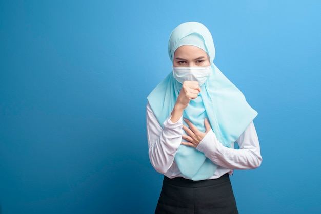 A young muslim woman with hijab wearing a surgical mask feeling sick and coughing over blue