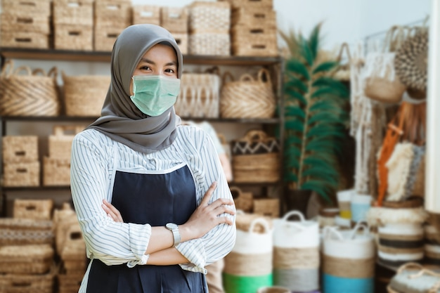 Young muslim woman with mask stand with crossed hands among handicraft items in craft galleries. business of asian woman with head scarf at shop. new open for business