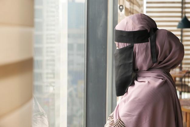Молодые мусульманские женщины закрывают лицо, глядя через окно в помещении