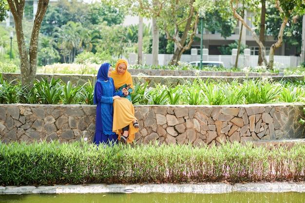 公園で休んでいる若いイスラム教徒の女性
