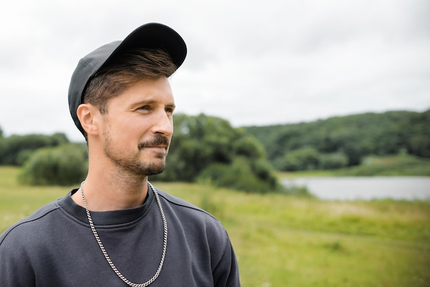 Young mustachioed man in a baseball cap outdoors. portrait of a guy looking to the side