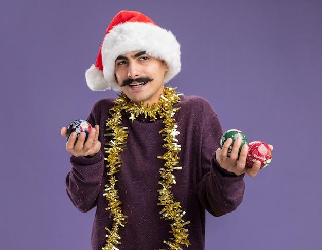 크리스마스 공을 들고 그의 목 주위에 반짝이와 크리스마스 산타 모자를 쓰고 젊은 mustachioed 남자 행복하고 긍정적 인 보라색 벽 위에 유쾌하게 서 웃고