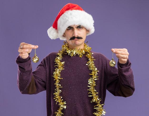 紫色の背景の上に立っている深刻な顔でカメラを見てクリスマスボールを保持している首に見掛け倒しのクリスマスサンタ帽子をかぶっている若い口ひげを生やした男