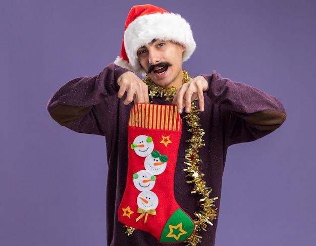 보라색 배경 위에 카메라를 놀라게하고 행복 서보고 크리스마스 스타킹을 들고 그의 목 주위에 반짝이와 크리스마스 산타 모자를 쓰고 젊은 mustachioed 남자
