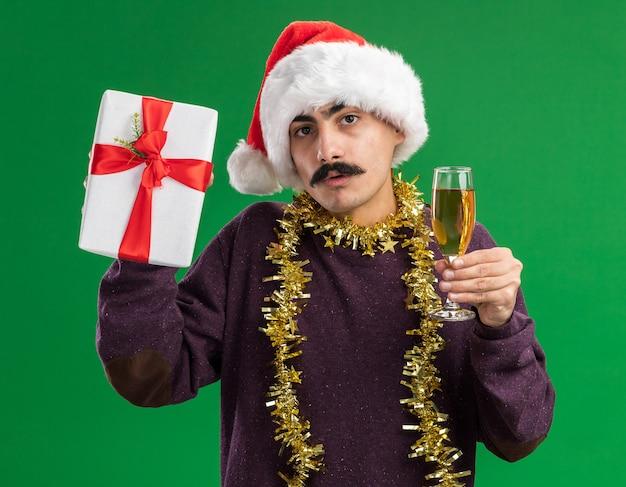 Молодой усатый мужчина в рождественской новогодней шапке с мишурой на шее с бокалом шампанского и рождественским подарком смотрит в камеру, смущенный стоя на зеленом фоне