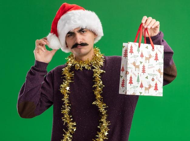 首に見掛け倒しのクリスマスサンタの帽子をかぶった若い口ひげを生やした男は、緑の背景の上に立って混乱し、非難されたカメラを見てクリスマスの贈り物と紙袋を保持しています