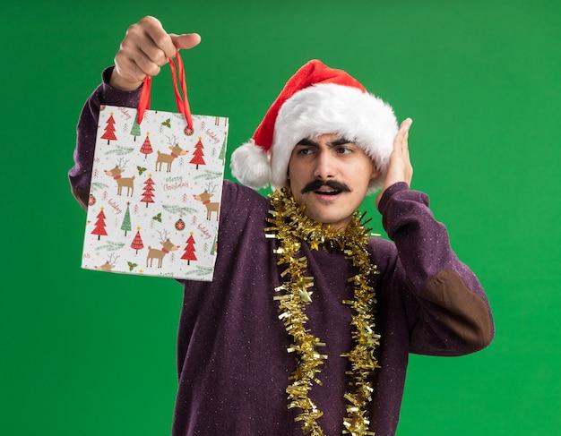 Молодой усатый мужчина в рождественской новогодней шапке с мишурой на шее держит бумажный пакет с рождественским подарком и смотрит на него в замешательстве и удивлении, стоя на зеленом фоне