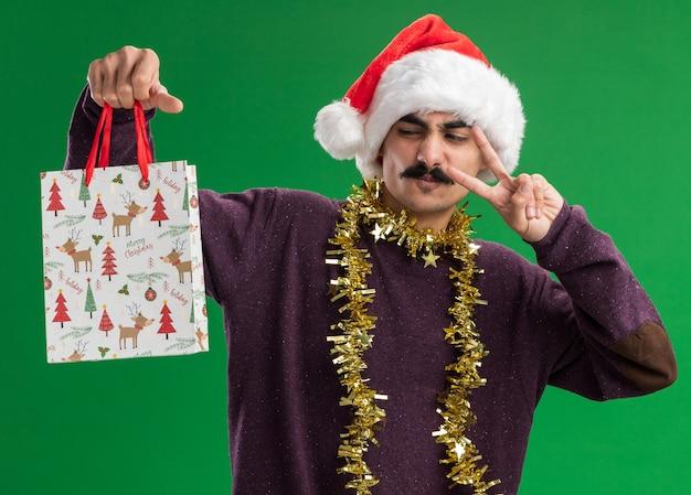 首に見掛け倒しのクリスマスサンタの帽子をかぶった若い口ひげを生やした男は、緑の背景の上に立っているvサインを示す幸せな顔でそれを見てクリスマスプレゼントと紙袋を保持しています