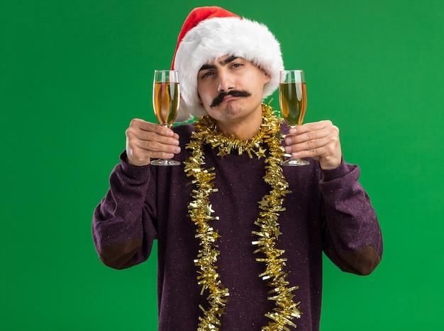 Молодой усатый мужчина в новогодней шапке санта-клауса с мишурой на шее, держа в руках два бокала шампанского, с уверенным выражением лица смотрит в камеру, стоя на зеленом фоне