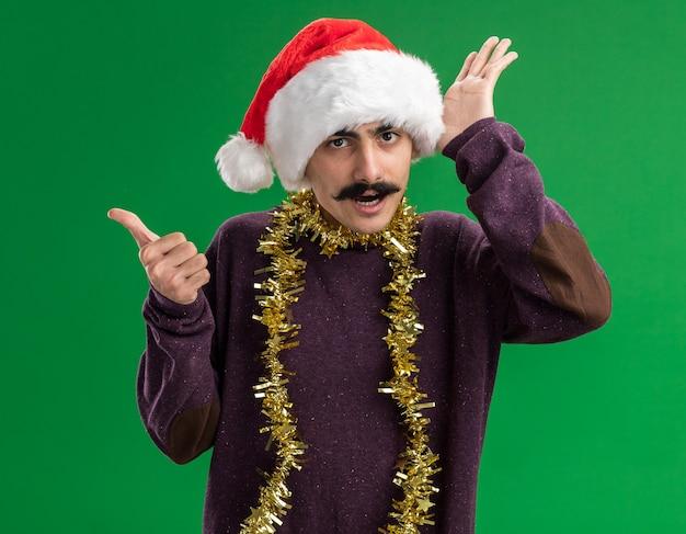 Молодой усатый мужчина в рождественской новогодней шапке с мишурой на шее смотрит в камеру, удивлен с поднятой рукой, указывающей назад, с большим пальцем, стоящим на зеленом фоне