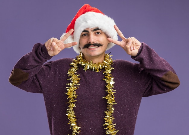 Young mustachioed man wearing christmas santa hat with tinsel around his neck looking at camera smiling cheerfully showing v-sign standing over purple background
