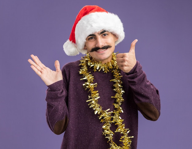 Giovane uomo baffuto indossando natale santa hat con orpelli intorno al collo guardando la fotocamera con il sorriso sul viso che presenta con il braccio della mano in piedi su sfondo viola