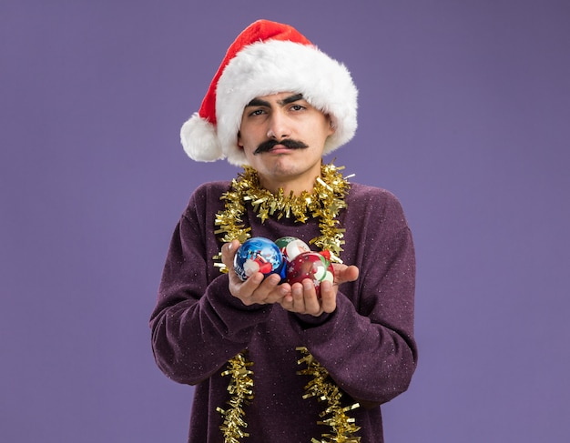 Young mustachioed man wearing christmas santa hat with tinsel around his neck showing christmas balls  confused  standing over purple wall