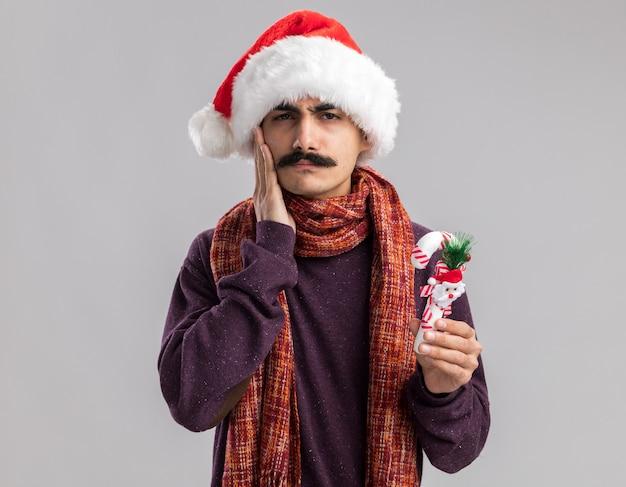 Giovane uomo baffuto che indossa il cappello della santa di natale con la sciarpa calda intorno al suo collo che tiene il bastoncino di zucchero di natale che sembra confuso