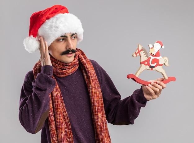 首に暖かいスカーフをかぶったクリスマスサンタの帽子をかぶった若い口ひげを生やした男は、それを見てクリスマスのおもちゃを持って混乱しています