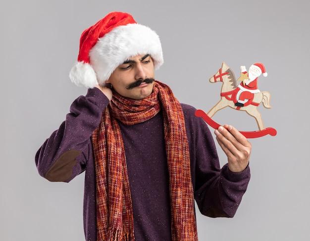 Giovane uomo baffuto che indossa il cappello di babbo natale con sciarpa calda intorno al collo tenendo il giocattolo di natale guardandolo confuso e molto ansioso in piedi su sfondo bianco