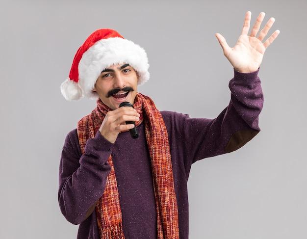 首に暖かいスカーフをかぶったクリスマスサンタの帽子をかぶった若い口ひげを生やした男は、白い背景の上に立って元気に腕を上げて笑顔でマイクを歌っています