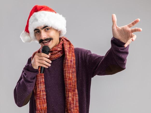 首に暖かいスカーフをかぶったクリスマスサンタの帽子をかぶった若い口ひげを生やした男は、白い壁の上に立って幸せで陽気な上げ腕を笑顔で歌うマイクを持っています