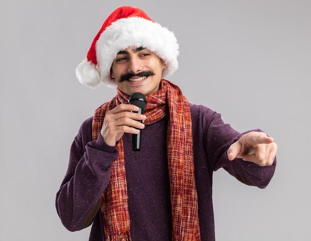 首に暖かいスカーフをかぶったクリスマスサンタの帽子をかぶった若い口ひげを生やした男は、白い壁の上に立っている側に人差し指で指しているマイクを笑顔で保持しています