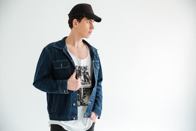 Giovane uomo misterioso in giacca con cappuccio e jeans
