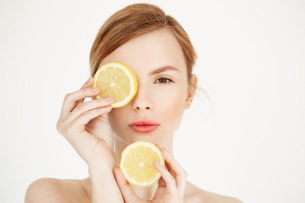 레몬 슬라이스 뒤에 눈을 숨기고 깨끗하고 건강한 피부를 가진 젊은 벌거 벗은 아름다운 소녀. 뷰티 스파 화장품.
