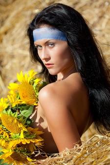 마른 건초에 서서 맑은 여름날에 해바라기로 몸을 덮고있는 젊은 벌거 벗은 갈색 머리 여자. 아름다움과 야생의 자연 개념