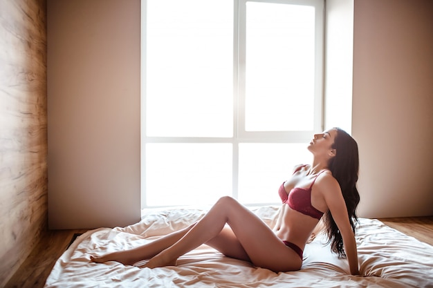 Young naked dark-haired woman on bed in morning.