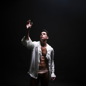 Young naked man in opened white shirt raising hand