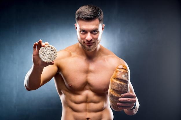 시리얼 크래커와 빵을 들고 젊은 벗은 몸통 남자 프리미엄 사진