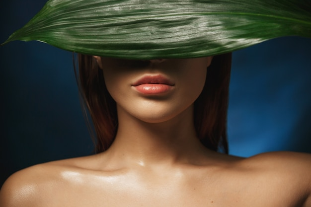 Young naked woman hiding face behind fresh green leave.