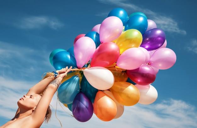 Молодая обнаженная женщина на пляже с разноцветными воздушными шарами