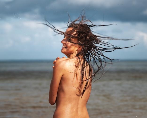 暗い嵐の空を背景に海のビーチでポーズをとって若い裸の女性