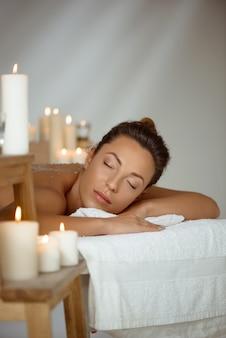 Молодая голая женщина расслабляющий в спа салоне.
