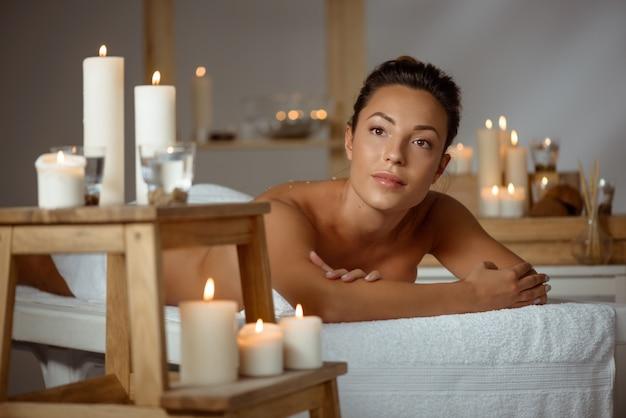 Giovane donna nuda che si distende nel salone della stazione termale.