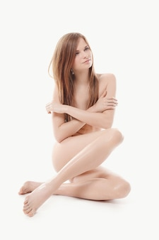 Young naked woman sitting on the floor, body and skin care concept