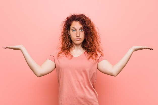 若い自然で本物の赤毛の女性は腕で鱗を作り、幸せで自信を持っています。
