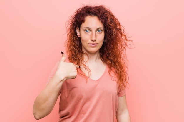 Young natural and authentic redhead woman person pointing by hand to a shirt copyspace, proud and confident